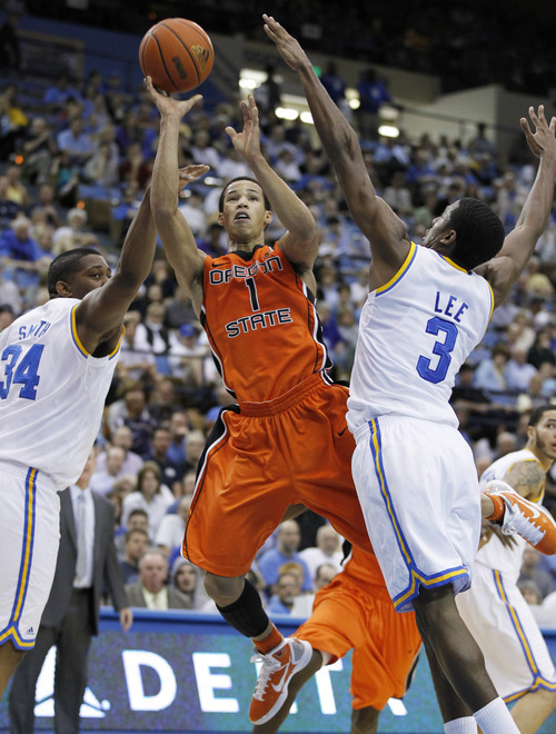 Danny Moloshok     The Associated Press Oregon State's Jared Cunningham, center, shoots between UCLA's Joshua Smith, left, and Malcolm Lee during the first half of an NCAA college basketball game in Los Angeles on Feb. 12, 2011.