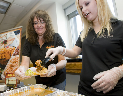 Al Hartmann     The Salt Lake Tribune Brenda Ricks, left, and Kate Cardell of Cafe Rio serve up some of their favorites on Tuesday for sampling: pork barbacoa and chili con queso with chips and guacamole. Salt Lake City International Airport officials showcased food samplings from several Salt Lake restaurants that will be opening outlets at the airport.