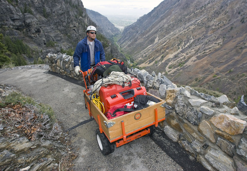 Al Hartmann  |  The Salt Lake Tribune Timpanogos Cave National National Monument maintanence worker Matt Thompson walks behind a front-wheel drive machine with supplies and equipment to construct a cable fence along an exposed part of the trail to the cave in American Fork Canyon. At right is a newly built rock wall.