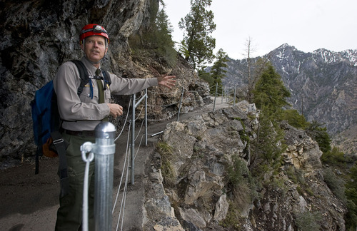 Al Hartmann  |  The Salt Lake Tribune Denis Davis, superintendent of Timpanogos Cave National National Monument in American Fork Canyon, checks out a new stretch of post and cable fencing along an exposed part of the trail.   The monument has made many safety improvements along the steep 1.5-mile trail leading to the cave in several dangerous areas in the wake of recent falls over the past few years, including the death of an employee last year.  The trail improvements are to be mostly finished this week as the cave opens for the 2011 season May 27.
