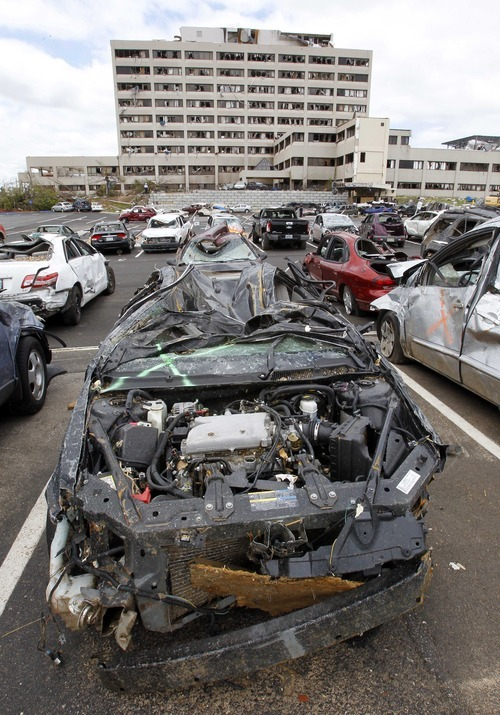 Destroyed cars sit in the parking lot of the damaged St. John's Regional Health Center on Thursday, May 26, 2011, in Joplin, Mo. A tornado tore through much of the city Sunday, wiping out neighborhoods and killing at least 125 people. (AP Photo/Mark Humphrey)