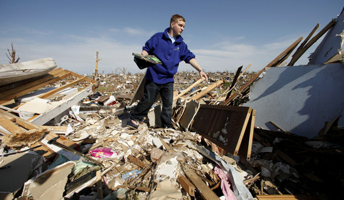 Brian Massengale looks for items in his destroyed home in Joplin, Mo. Friday, May 27, 2011. An EF-5 tornado tore through much of the city Sunday, damaging a hospital and hundreds of homes and businesses and killing at least 126 people. (AP Photo/Charlie Riedel)
