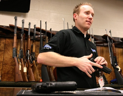 Leah Hogsten  |  The Salt Lake Tribune The sales manager of Doug's Shoot 'N Sports sells a handgun Saturday in Taylorsville. Sales of guns at gun shops in Utah are closely regulated, but those selling firearms over the Internet through classifieds have few restrictions or regulations.