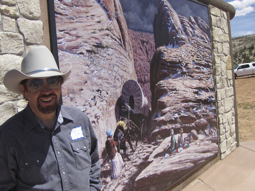 Mark Havnes  |  The Salt Lake Tribune Escalante artist Lynn Griffin on Saturday next to a weather-resistant mural of one of his paintings of Utah pioneers descending the Hole in the Rock. The mural is part of a display at the first phase of the Hole in the Rock Escalante Heritage Center dedicated on Saturday.