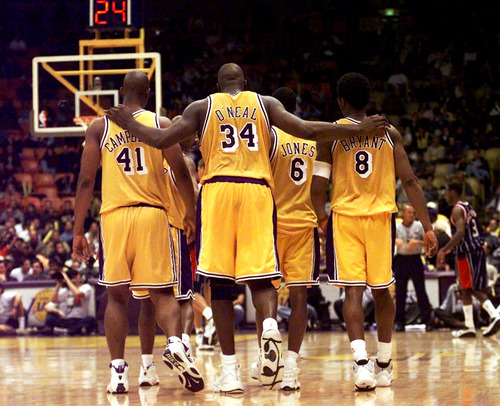 This Feb. 5, 1999 file photo shows Los Angeles Lakers center Shaquille O'Neal (34) putting his arms around teammates, Elden Campbell (41) and Kobe Bryant (8) as Eddie Jones (6) and Derek Harper walk in front as they return to play the Houston Rockets in the fourth quarter at the Great Western Forum in Inglewood, Calif. O'Neal says on Twitter that he's