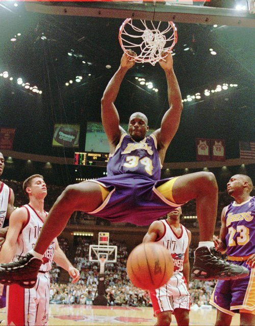 This Nov. 12, 1996, file photo shows Los Angeles Lakers' Shaquille O'Neal (34) hanging from the rim after a dunk during the third quarter against the Houston Rockets,  in Houston.  O'Neal says on Twitter that he's