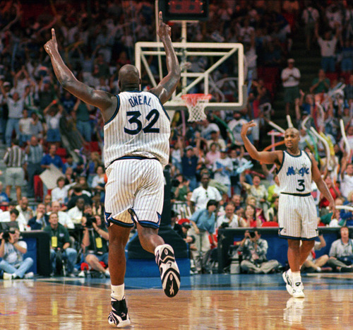 This April 28, 1996 file photo shows Orlando Magic center Shaquille O'Neal (32) running down the court giving the number one sign after making a slam dunk during the final minutes of the Magic's 92-77 win in game two of the Eastern Conference Quarterfinals against he Detroit Pistons in Orlando.  Helping celebrate is Dennis Scott (3).  O'Neal says on Twitter that he's