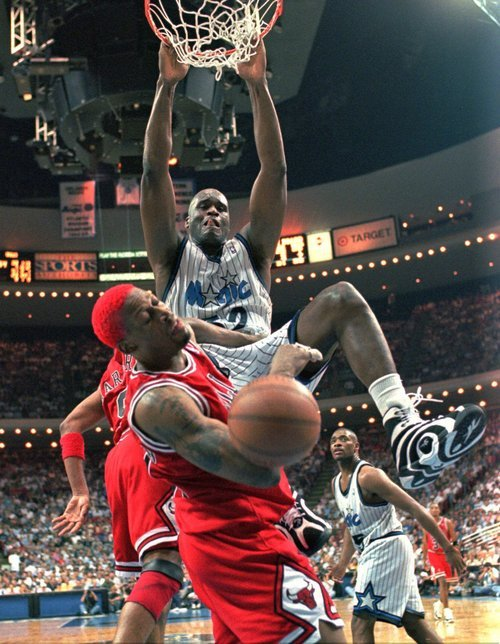 This April 7, 1996 file photo shows Orlando Magic's Shaquille O'Neal  dunking the ball and knocking Chicago Bulls' Dennis Rodman out of the way at the same time during their game in Orlando.  O'Neal says on Twitter that he's