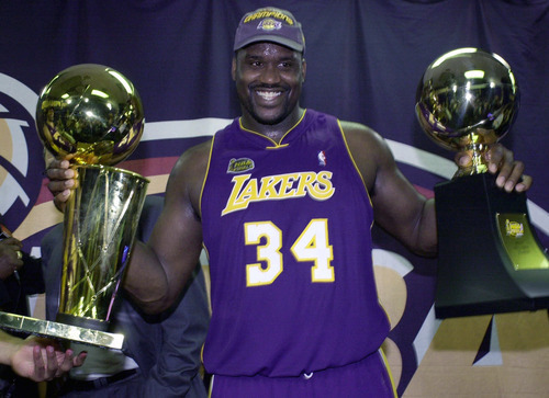 This June 15, 2001 file photo shows Los Angeles Lakers' Shaquille O'Neal holding up the MVP trophy, right, and the championship trophy after the Lakers won their second straight NBA championship in Philadelphia.  O'Neal says on Twitter  Wednesday June 1, 2001, that he's