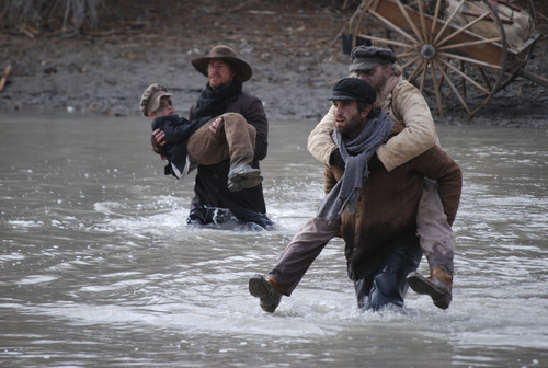 Levi Savage (Jasen Wade, left) and George Padley (Jason Celaya, right) carry Mormon settlers across the Platte River during a treacherous handcart journey to Utah in the drama