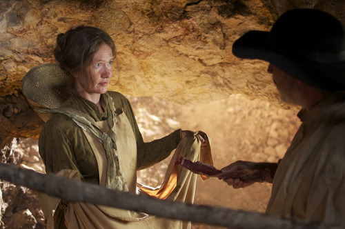 Mormon settler Elizabeth Panting (Emily Wadley, left) accepts life-saving jerky from a stranger, one of the miracles depicted on the pioneer trail in the drama