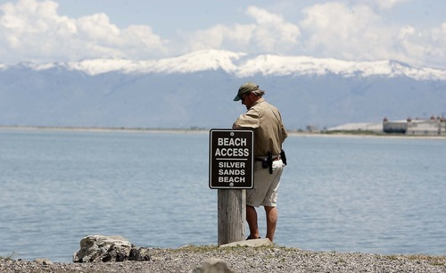 Trent Nelson     The Salt Lake Tribune Dave Shearer, harbor master of the Great Salt Lake Marina, stands Wednesday at the access point to Silver Sands Beach. As recently as November, 2010, the beach area visible to the right of Shearer, all the way to Saltair in the background, was dry land.