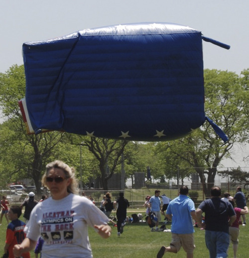 In this June 4, 2011, photo, participants in an Oceanside, N.Y., soccer tournament run from an airborne inflatable