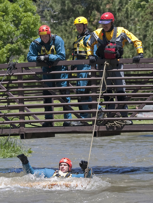 Margaret Distler  |  The Salt Lake Tribune  Shane Conrad and Jared Christensen watch alongside Jeff Ellis as Mike Jones completes the strainer drill during Swift Water Rescue Training in Murray City Park on Tuesday. Participants wore dry suits to keep warm as they rotated through three different drills stationed along Little Cottonwood Creek.