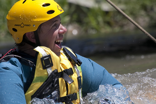 Margaret Distler  |  The Salt Lake Tribune Jared Christensen smiles as he completes the strainer drill during Swift Water Rescue Training in Murray City Park on Tuesday. Participants wore dry suits to keep warm as they rotated through three different drills stationed along Little Cottonwood Creek.