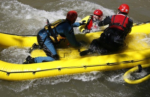 Trent Nelson  |  The Salt Lake Tribune  Shane Conrad, left, and Scott Pearson, right, pull in Tyler Ownsbey during swift-water rescue training in Murray Park on Tuesday. Six fire departments were on hand for the training session.