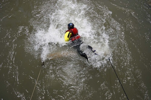 Trent Nelson  |  The Salt Lake Tribune  Dave Mills, of the Midvale Fire Department, swims over an obstacle during swift-water rescue training in Murray Park on Tuesday. Six fire departments were on hand for the training session.