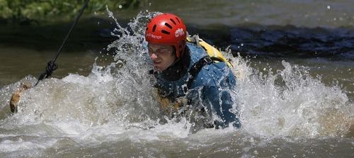 Trent Nelson  |  The Salt Lake Tribune  Mike Jones, of the South Salt Lake Fire Department, swims over an obstacle during swift-water rescue training in Murray Park on Tuesday. Six fire departments were on hand for the training session.