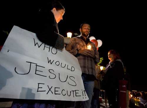 Kristin Powers, left, of Salt Lake City, holds a sign that reads