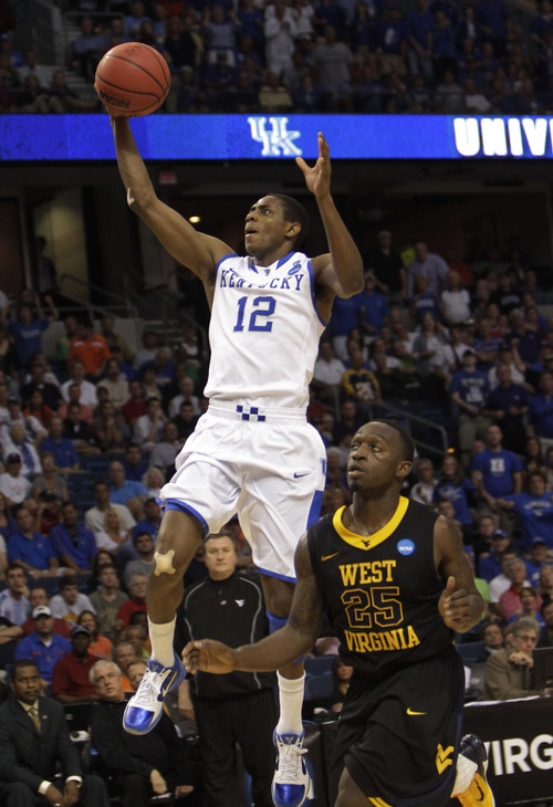 Kentucky's Brandon Knight (12) soares to the basket over West Virginia's Darryl Bryant (25) during the second half of a third-round East regional NCAA basketball game in Tampa, Fla., Saturday March 19, 2011. Kentucky defeated West Virginia 71-63. (AP Photo/John Raoux)