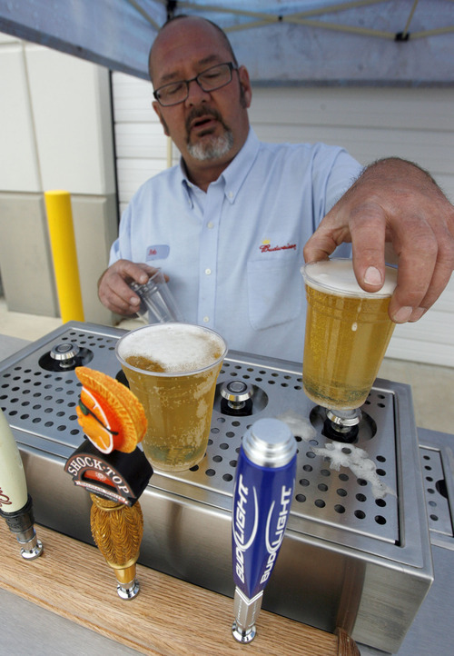 Francisco Kjolseth  |  The Salt Lake Tribune Rob Hammer, a senior draught technician, demonstrates how the new Bottoms Up beer dispenser shoots beer into a cup from the bottom to pour a more efficient cup of beer.