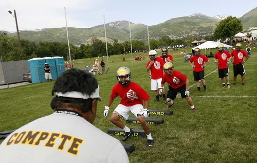 Trent Nelson  |  The Salt Lake Tribune University of Wyoming assistant coach Mike Fanoga leads drills Thursday at the All-Poly football camp, held at Millcreek Junior High School.