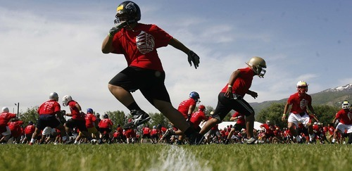 Trent Nelson  |  The Salt Lake Tribune High school football players run drills Thursday at the All-Poly Football Camp, held at Millcreek Junior High School.