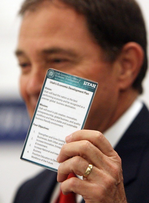 Steve Griffin  |  The Salt Lake Tribune  Utah Governor Gary Herbert holds up a card Monday that he carries in his pocket that outlines Utah's economic plan. He showed it during an announcement of significant job increases by two Utah companies.