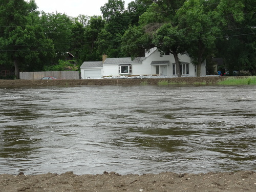 The Souris River passes near a home Tuesday, June 21, 2011, in Minot, N.D. About 11,000 Minot residents are being ordered to leave their homes even earlier than expected this week as the river gets closer to swamping the North Dakota city with the worst flooding in four decades, officials said Tuesday. (AP Photo/ The Forum, Teri Finneman)