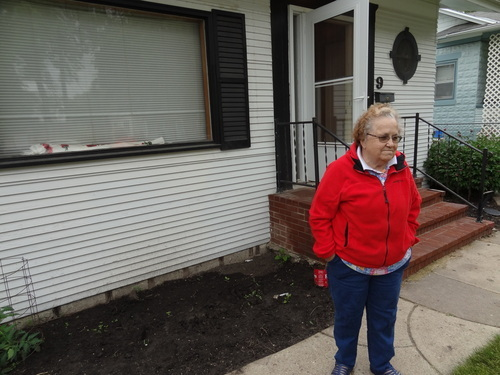 Tina Collom, 82, stands outside her Minot, N.D., home shortly before leaving it, Tuesday, June 21, 2011. Her home flooded in the 1969 flood and now faces flooding again.