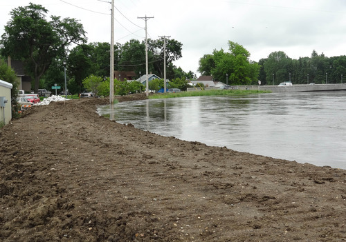 The rising Souris River passes through Minot, N.D., Tuesday, June 21, 2011. About 11,000 Minot residents are being ordered to leave their homes even earlier than expected this week as the Souris River gets closer to swamping the North Dakota city with the worst flooding in four decades, officials said Tuesday. Water is expected to reach the top of city's levees within the next two days and the resulting flooding is expected to dwarf the historic flood of 1969. (AP Photo/ The Forum, Teri Finneman)