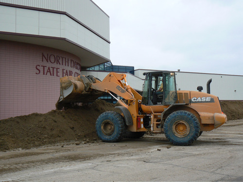 Dike work began late Monday, June 20 to protect the North Dakota State Fair Center in Minot, N.D. The rising level of the Souris River is expected to inundate the State Fairgrounds, which are located in east Minot.  (AP Photo/Minot Daily News, Kim Fundingsland)