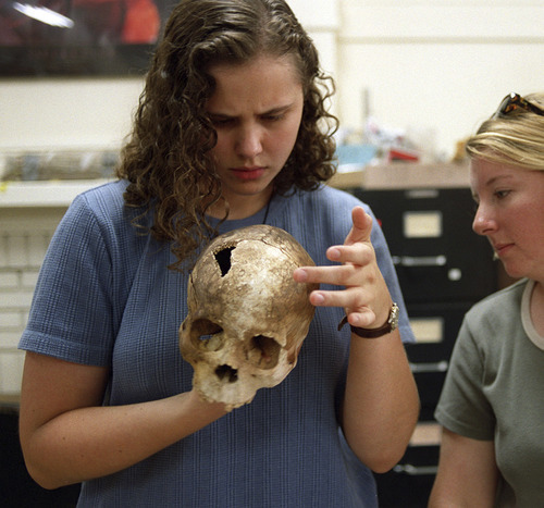 U of U anthropology students Derinna Kopp and Laurel Heap examine the 100-year-old bones of a bboy who died in a cave near St. George. Kopp was laid off from the Utah Department of Community and Culture on Tuesday, along with two other anthropologists.