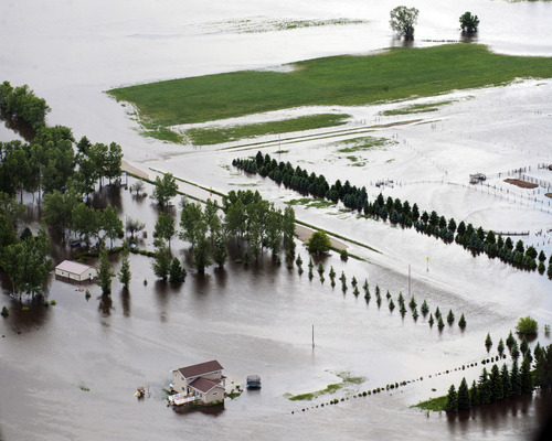 Flooding from the Souris river sweeps across the landscape on the outskirts of Minot, N.D., Wednesday afternoon June 22, 2011. As many as 10,000 people raced to evacuate Wednesday as water began spilling over Minot's levees. The river, which begins in the Canadian province of Saskatchewan and flows for a short distance though North Dakota, was all but certain to inundate thousands of homes and businesses during the next week. (AP Photo/The Grand Forks Herald, Christian Randolph)