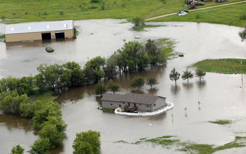 A farm is covered in water near Minot, N.D. on Wednesday, June 22, 2011. As many as 10,000 people raced to evacuate Wednesday as water began spilling over Minot's levees. The river, which begins in the Canadian province of Saskatchewan and flows for a short distance though North Dakota, was all but certain to inundate thousands of homes and businesses during the next week. (AP Photo/Will Kincaid)