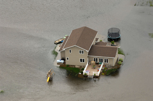 A home is surrounded by water near Minot, N,D. on Wednesday, June 22, 2011. As many as 10,000 people raced to evacuate Wednesday as water began spilling over Minot's levees. The river, which begins in the Canadian province of Saskatchewan and flows for a short distance though North Dakota, was all but certain to inundate thousands of homes and businesses during the next week. (AP Photo/Will Kincaid)