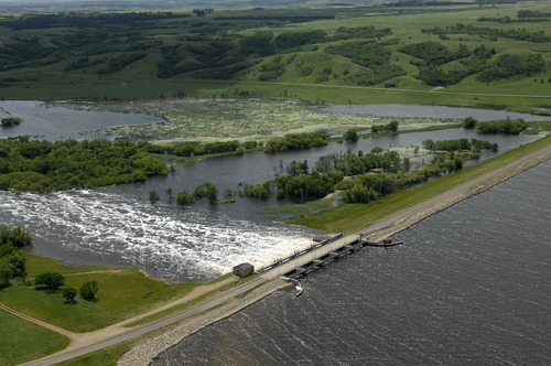 Water flows from Lake Darling into the Souris River on Wednesday, June 22, 2011. Lake Darling is located about fifteen miles north of Minot, ND.  As many as 10,000 people raced to evacuate Wednesday as water began spilling over Minot's levees. The river, which begins in the Canadian province of Saskatchewan and flows for a short distance though North Dakota, was all but certain to inundate thousands of homes and businesses during the next week. (AP Photo/Will Kincaid)