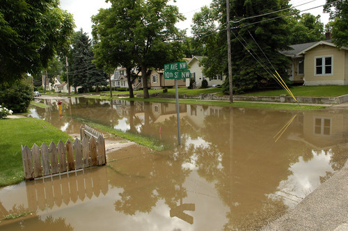 Water fills the streets in the Oak Park neighborhood of  Minot, N.D. on Wednesday, June 22, 2011.  As many as 10,000 people raced to evacuate Wednesday as water began spilling over Minot's levees. The river, which begins in the Canadian province of Saskatchewan and flows for a short distance though North Dakota, was all but certain to inundate thousands of homes and businesses during the next week.  (AP Photo/Will Kincaid)