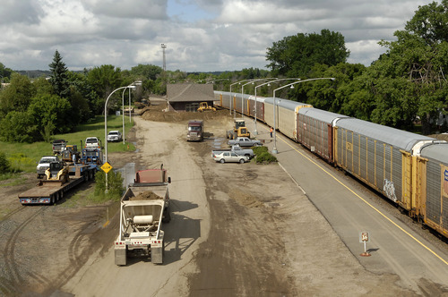 Construction crews build a dike around the Amtrak station as a freight train pass by in Minot, N.D. on Wednesday, June 22, 2011. Officials expect the the train tracks will be under several feet of water in the next few days. (AP Photo/Will Kincaid)
