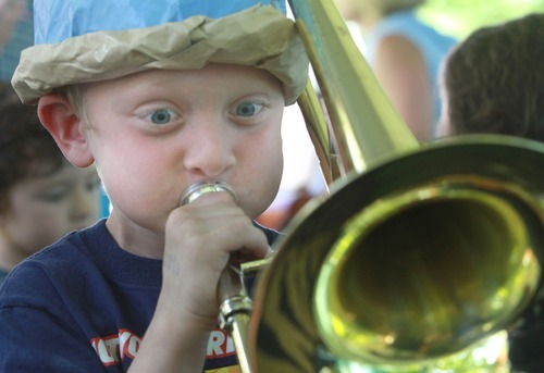 Rick Egan   |  The Salt Lake Tribune Mason Chivers, 7, Herriman, toots a trombone at the Instrument Petting Zoo.