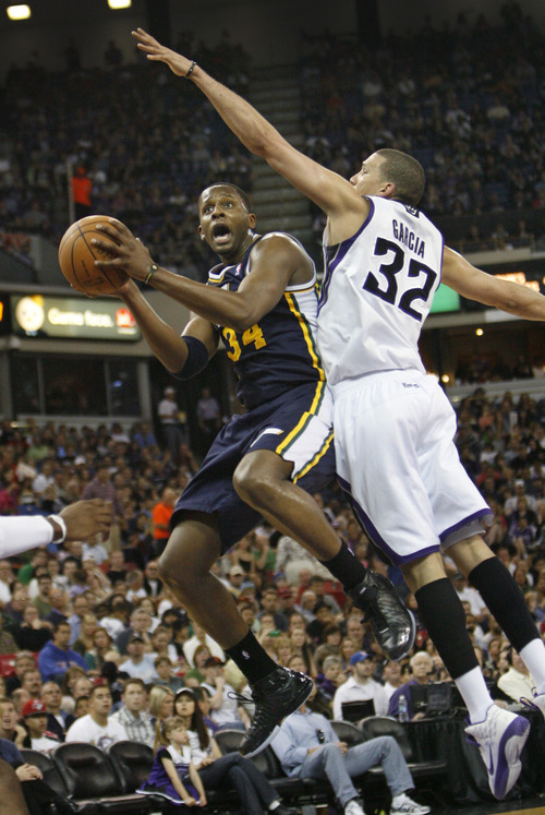 Utah Jazz forward C.J. Miles, left, shoots against Sacramento Kings defender Francisco Garcia during the first half of an NBA basketball game in Sacramento, Calif., Sunday, April 3, 2011. (AP Photo/Steve Yeater)