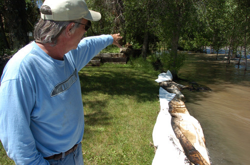 Jim Swanson points upstream where an ExxonMobil pipeline ruptured beneath the Yellowstone River, causing a spill that stretched dozens of miles down the river, Saturday July 2, 2011 in Laurel, Mont. (AP Photo/Matthew Brown)