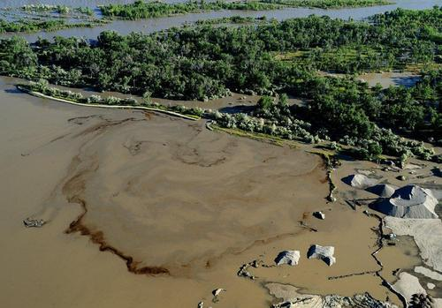 Oil swirls in a flooded gravel pit in Lockwood, Mont. after a pipeline break early Saturday, July 2, 2011. The ExxonMobil pipeline that runs under the Yellowstone River near Billings in south-central Montana ruptured and dumped an unknown amount of oil into the waterway, prompting temporary evacuations along the river. (AP Photo/The Billings Gazette, Larry Mayer)