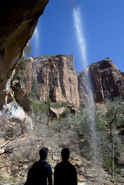 Tribune file photo Visitors at Zion National Park stop and take in a waterfall cascading over a sandstone overhang along the Emerald Pool Trail.