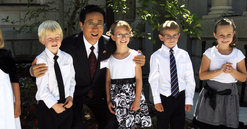 Pool photo  |  The Associated Press Zhao Hong Zhu, party secretary of Zhejiang Province, poses for a quick photo with a group of singers from East Lake Elementary prior to a luncheon hosted by Gov. Gary Herbert for the Chinese governors' delegation Thursday.