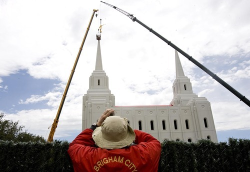 Djamila Grossman  |  The Salt Lake Tribune  Gerry Ferguson of Brigham City takes pictures as workers hoist a statue of the angel Moroni atop the new Brigham City Temple of The Church of Jesus Christ of Latter-day Saints on Tuesday, July 12, 2011.