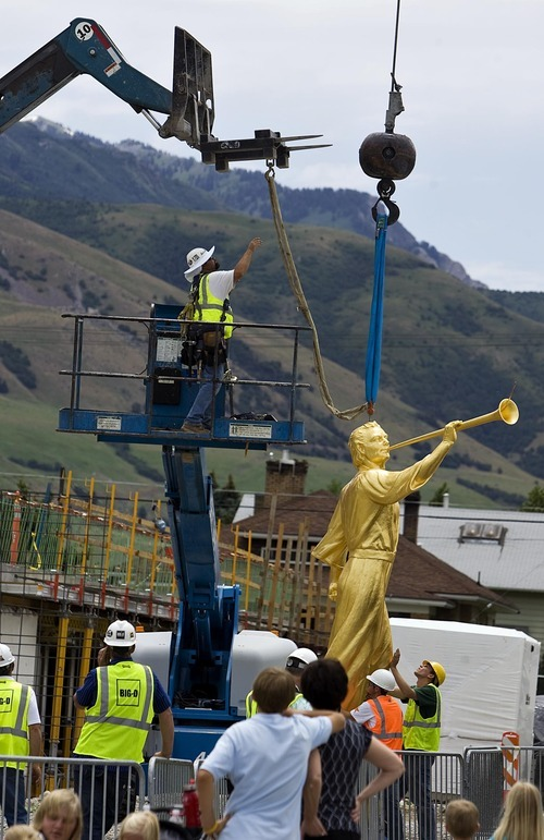 Djamila Grossman  |  The Salt Lake Tribune  Workers prepare a statue of the angel Moroni before hoisting it atop the new Brigham City Temple of The Church of Jesus Christ of Latter-day Saints on Tuesday, July 12, 2011.
