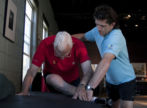 Margaret Distler  |  The Salt Lake Tribune  Paul Holbrook, owner of Age Performance personal training studio, assists Ted Belknap with a hip stretch with rotation exercise during Belnap's workout session on Tuesday, June 21, 2011.