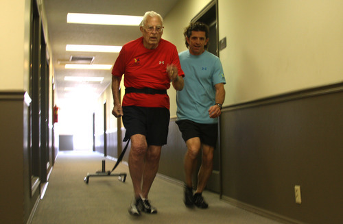 Margaret Distler  |  The Salt Lake Tribune  Paul Holbrook, owner of Age Performance personal training studio, runs alongside Ted Belknap as he pulls a sled down a hallway outside the studio during Belknap's workout session on Tuesday, June 21, 2011. Belknap's training includes various exercises, like this one intended for speed, in preparation for competing in the 50-meter-dash at the Huntsman Senior Games this summer.