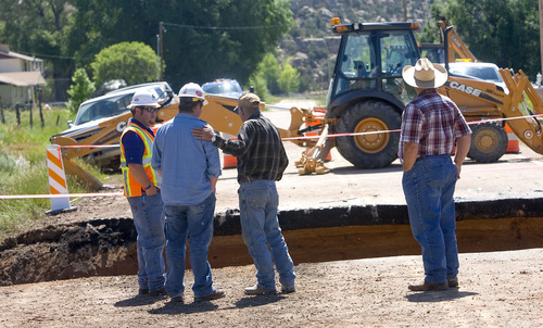 Al Hartmann  |  The Salt Lake Tribune Road contractors check out a 25-foot-deep 40-foot-wide hole on Highway 35 about 3 miles south of Tabiona that was the site of a fatal accident Wednesday night.